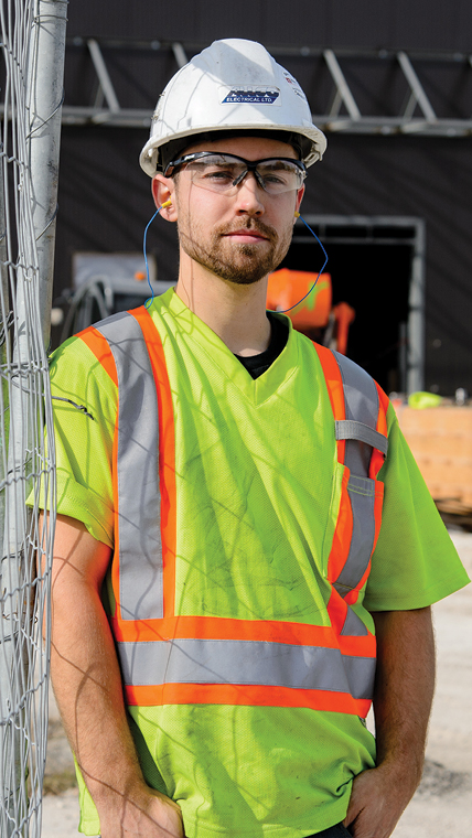 Young male construction worker in white hard hat and high-visibility shirt on a job site.